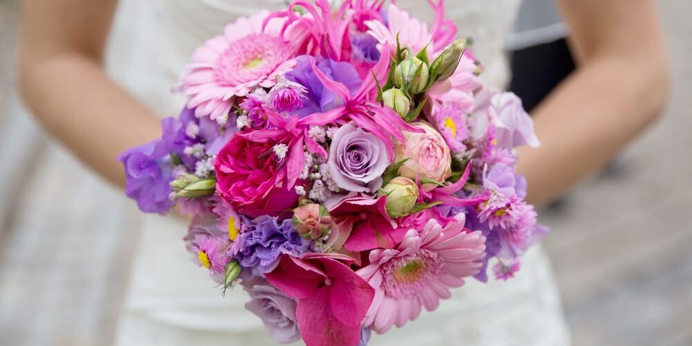 Eine Braut hält einen Blumenstrauß.