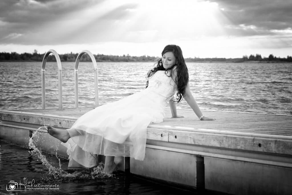 Eine Braut badet mit den Füßen im Wasser
