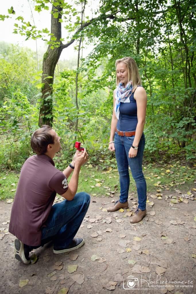 Mann geht vor seiner Frau auf die Knie und macht ihr einen Antrag