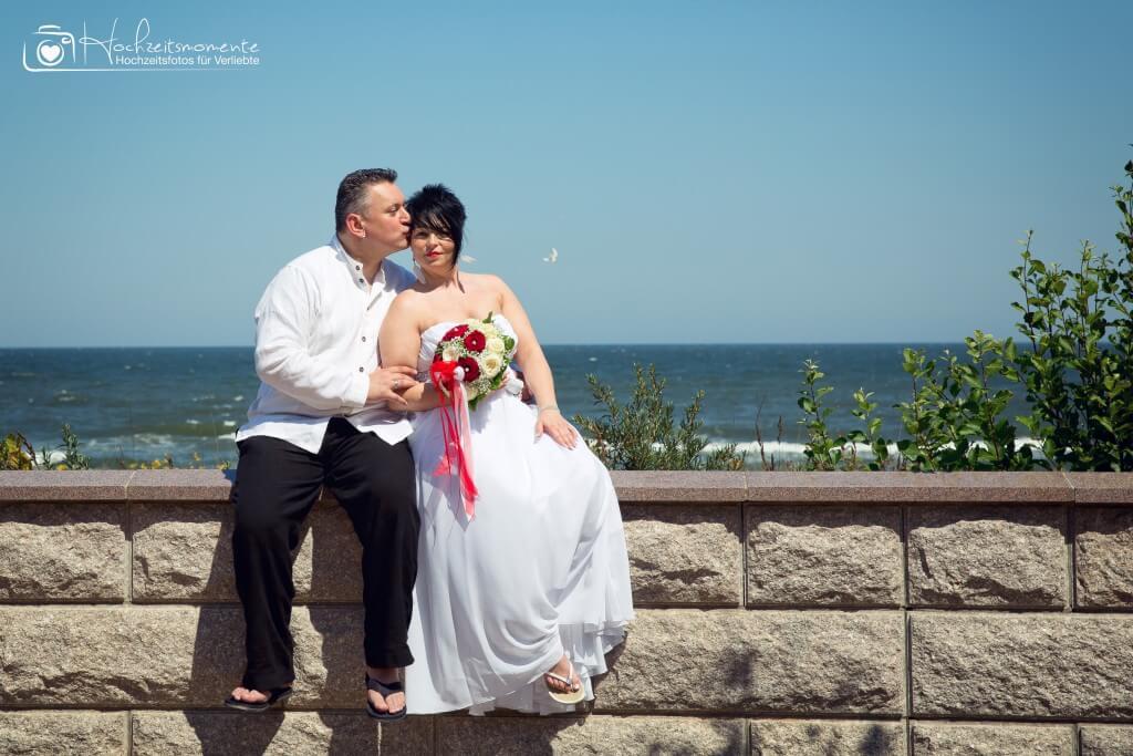 Brautpaar sitzt auf einer Mauer