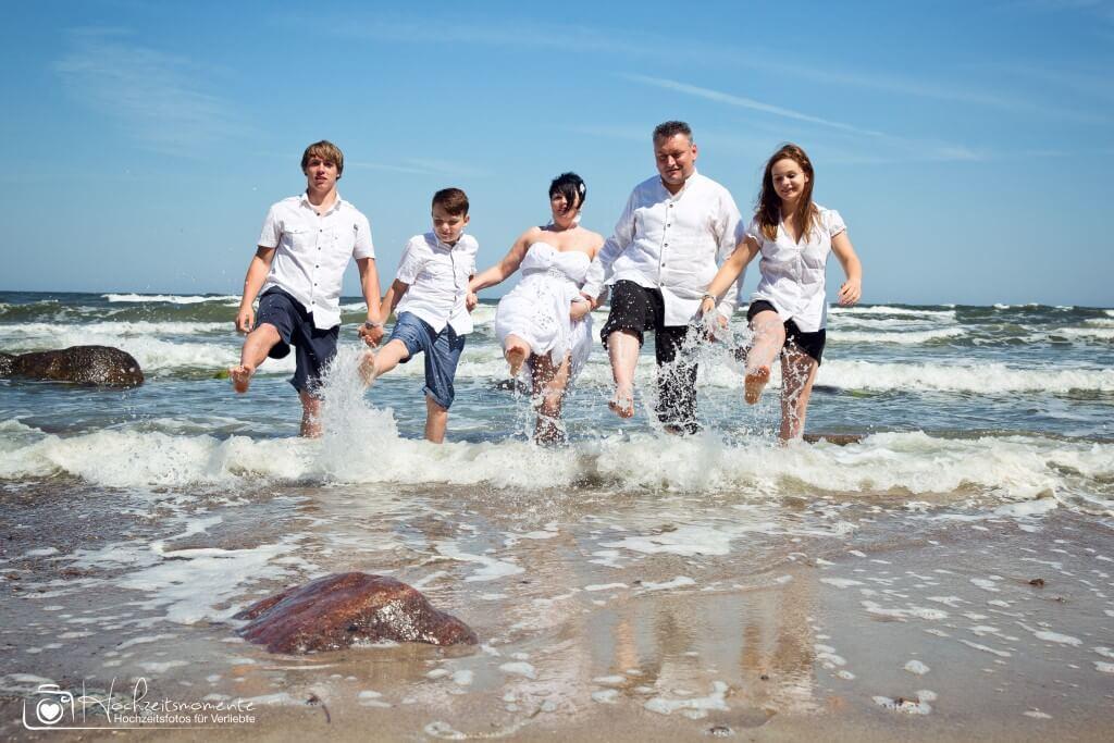 Familie spritzt mit Ostsee Wasser