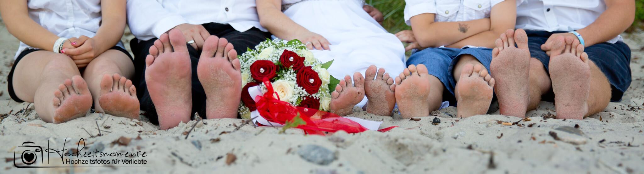 Füße von fünf Personen am Ostsee-Strand