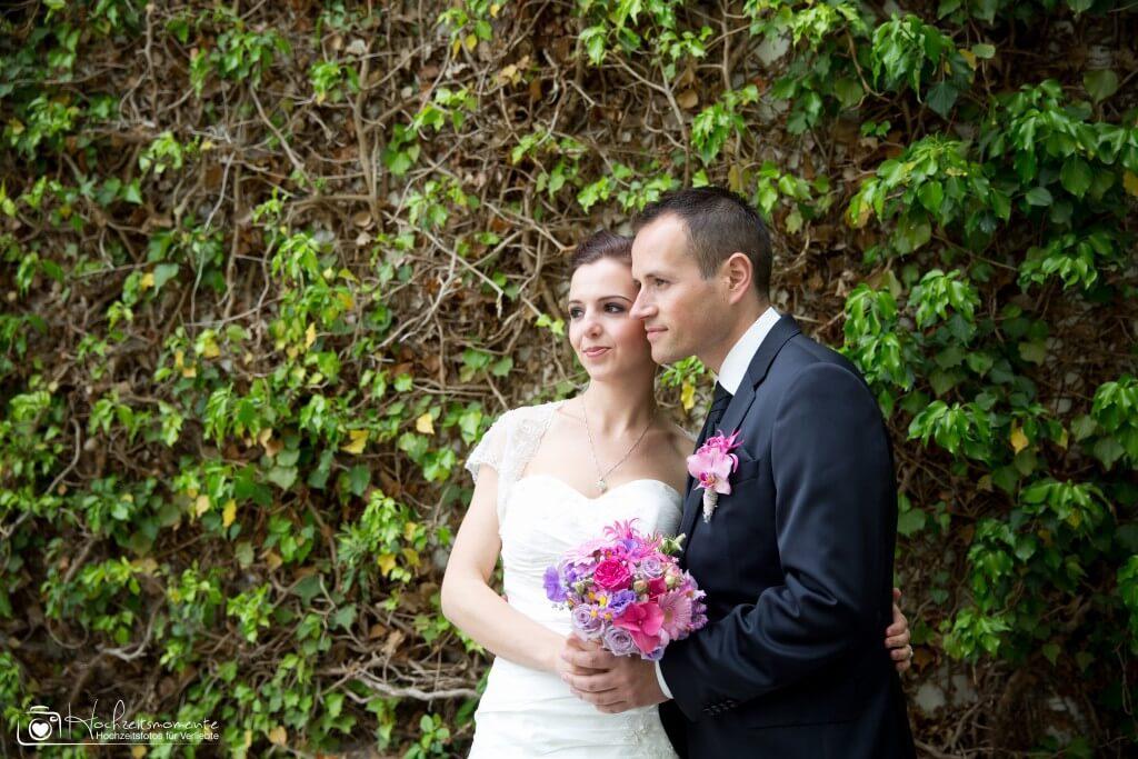 Hochzeitsfoto vor einem Strauch