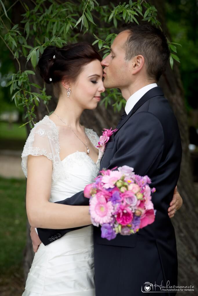 Bräutigam küsst Braut auf die Stirn.
