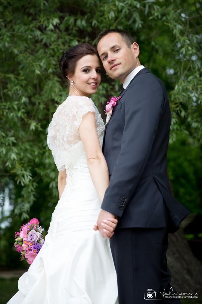 Ein Hochzeitsfotos mit Blick von unten auf ein Brautpaar.