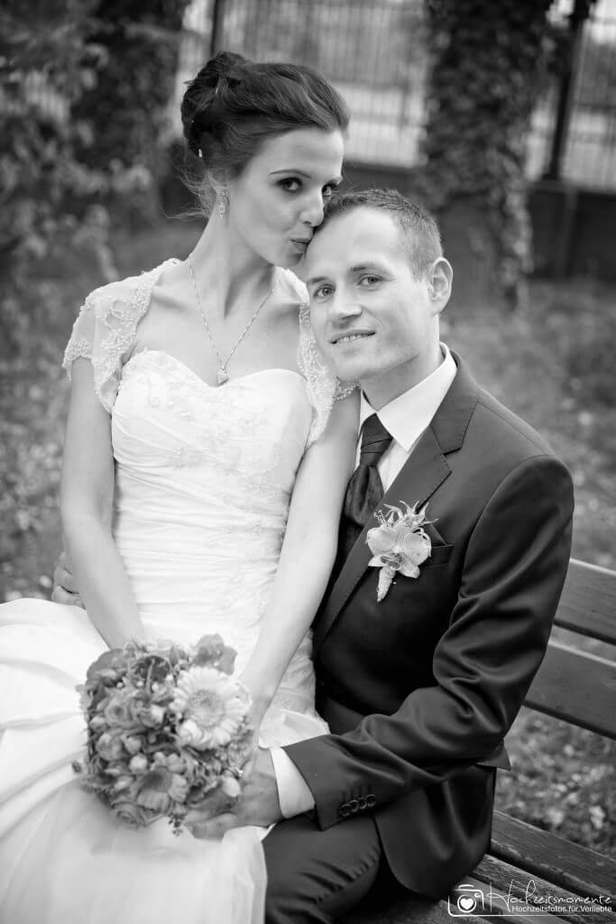 Ein Ehepaar sitzt nach der Hochzeit an der Ostsee auf einer Bank