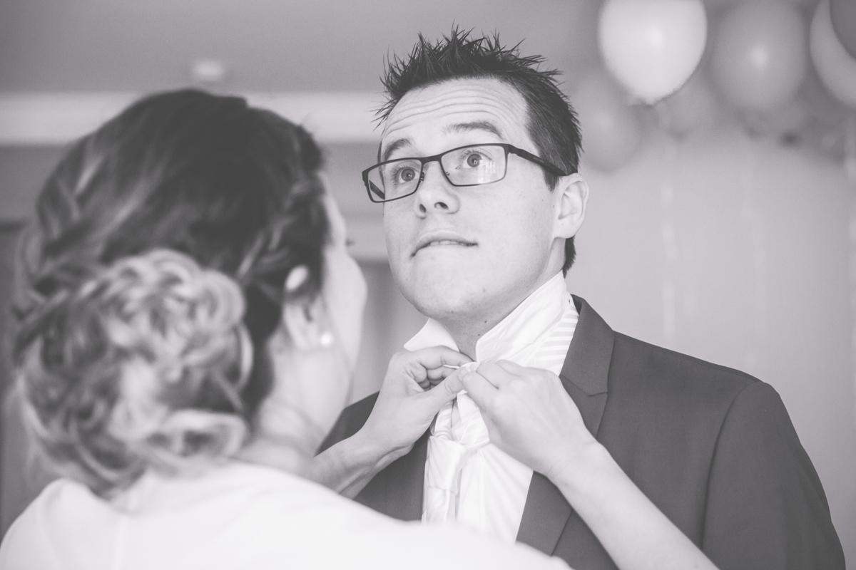 Braut bindet Bräutigam die Krawatte