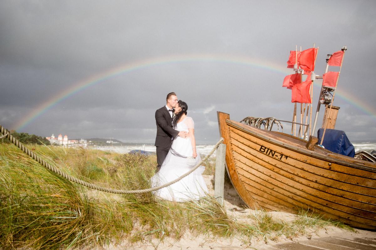 Am Strand steht das Brautpaar mit Regenbogen