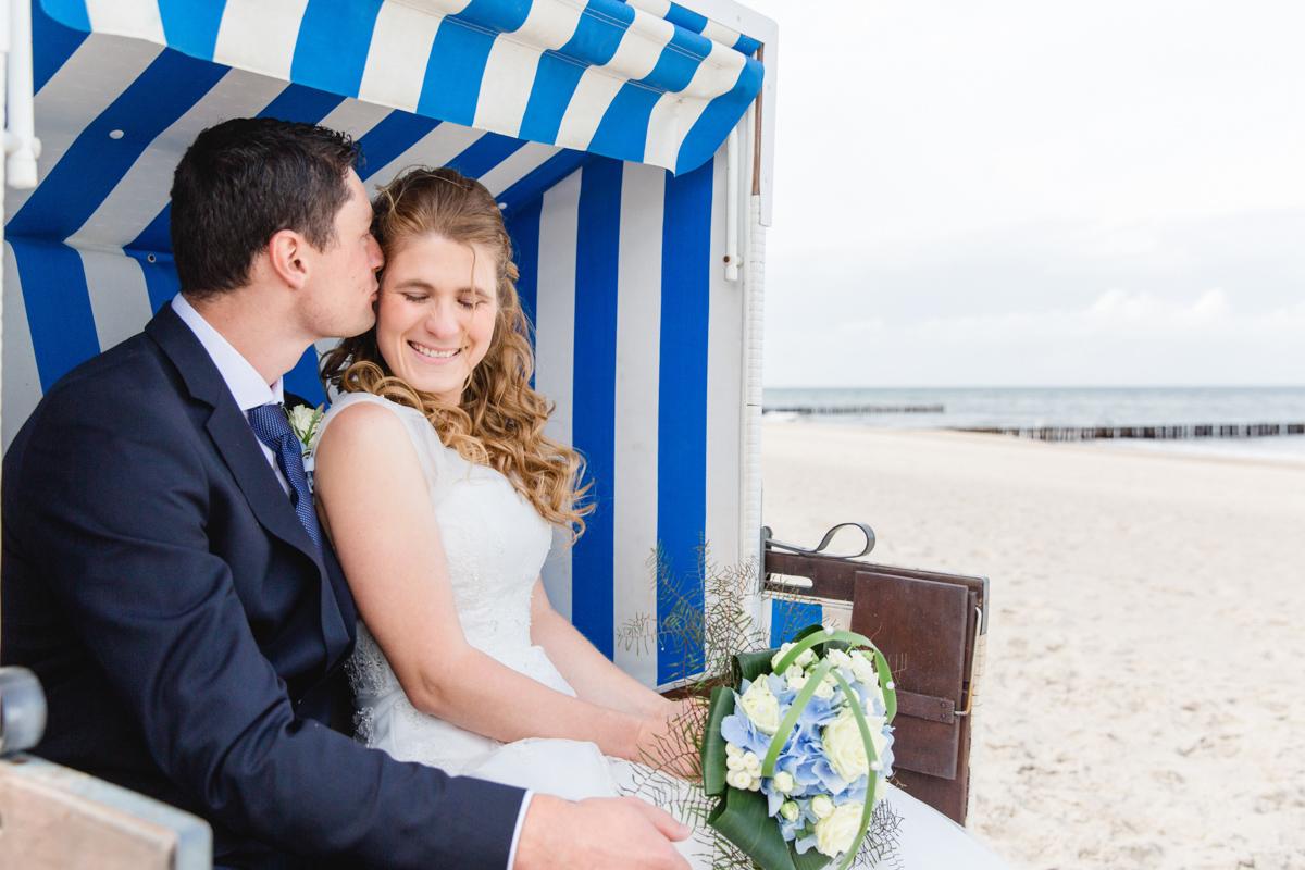 Küssendes Brautpaar im Strandkorb