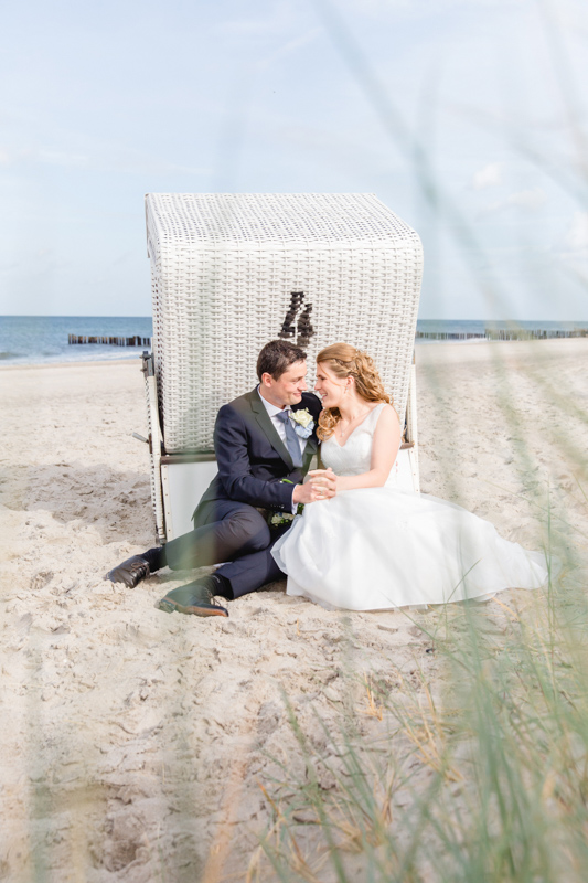 Brautpaar kuschelt vor einem Strandkorb