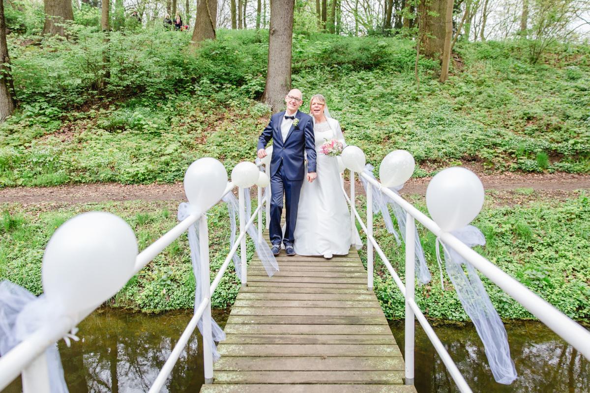 Braut und Bräutigam gehen gemeinsam zur Trauung auf dem Landgut Lischow.