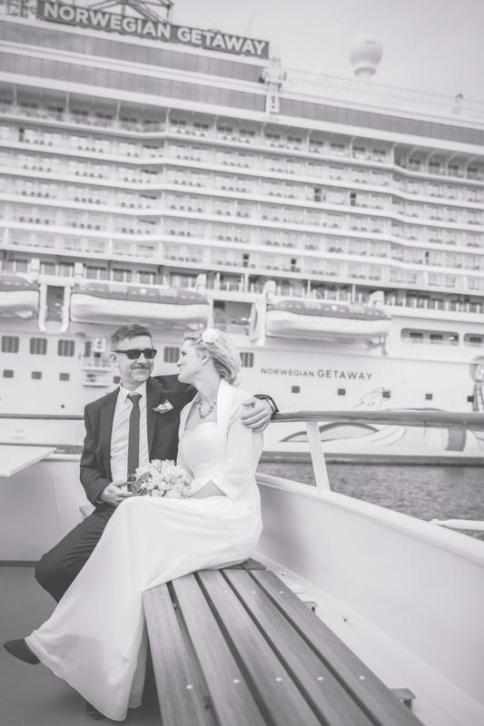 Auf dem Foto sieht man ein Brautpaar vor einem Kreuzfahrtschiff.