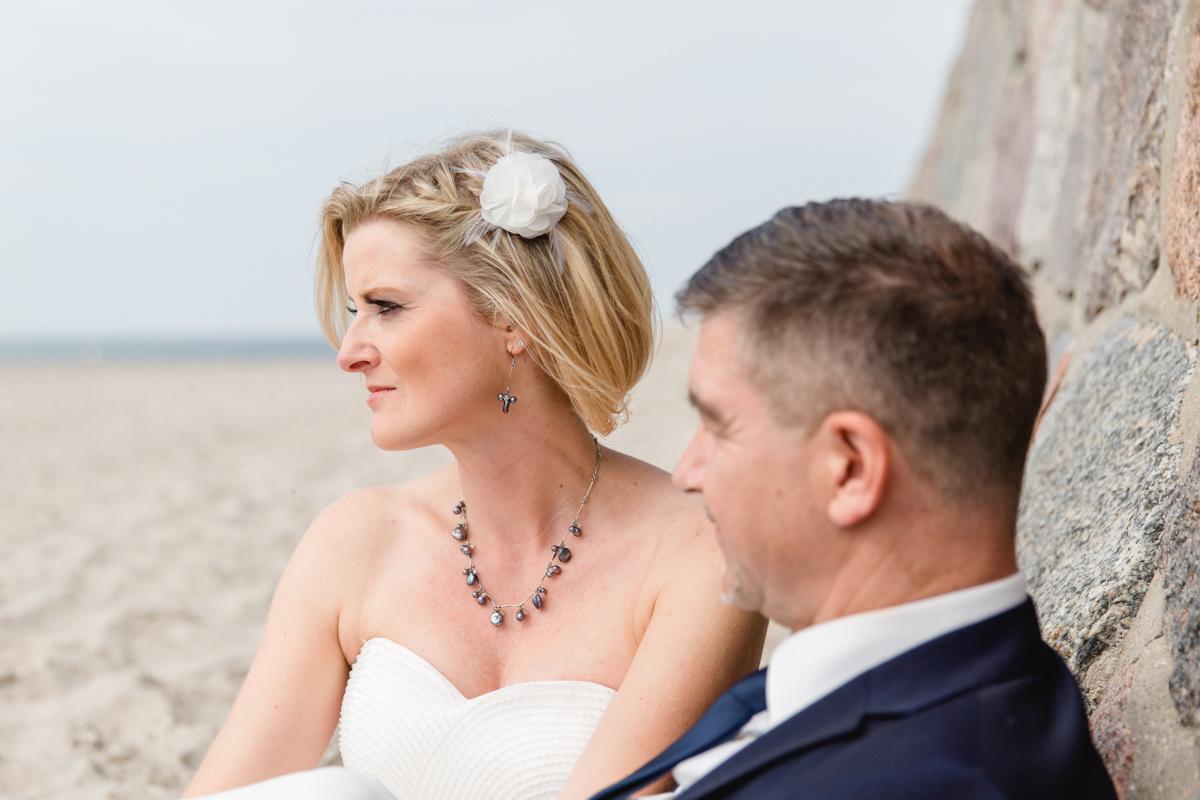 Brautpaar sitzt am Strand von Warnemünde.