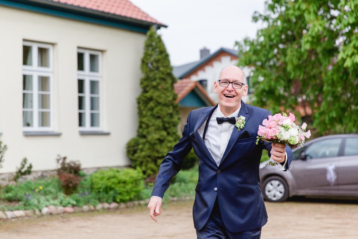 Bräutigam eilt mit dem Brautstrauß heran.