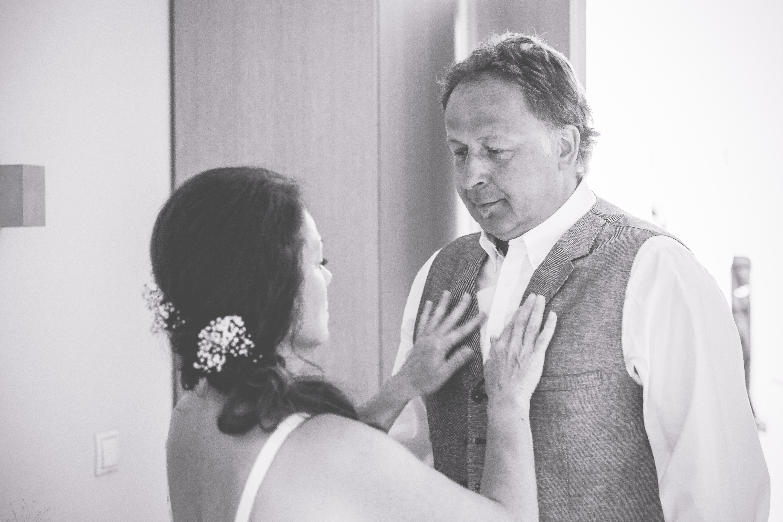 Braut hilft Bräutigam beim Fertigmachen.