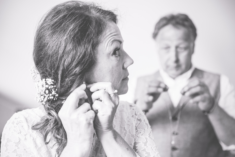 Braut legt ihre Ohrringe für die Hochzeit an.
