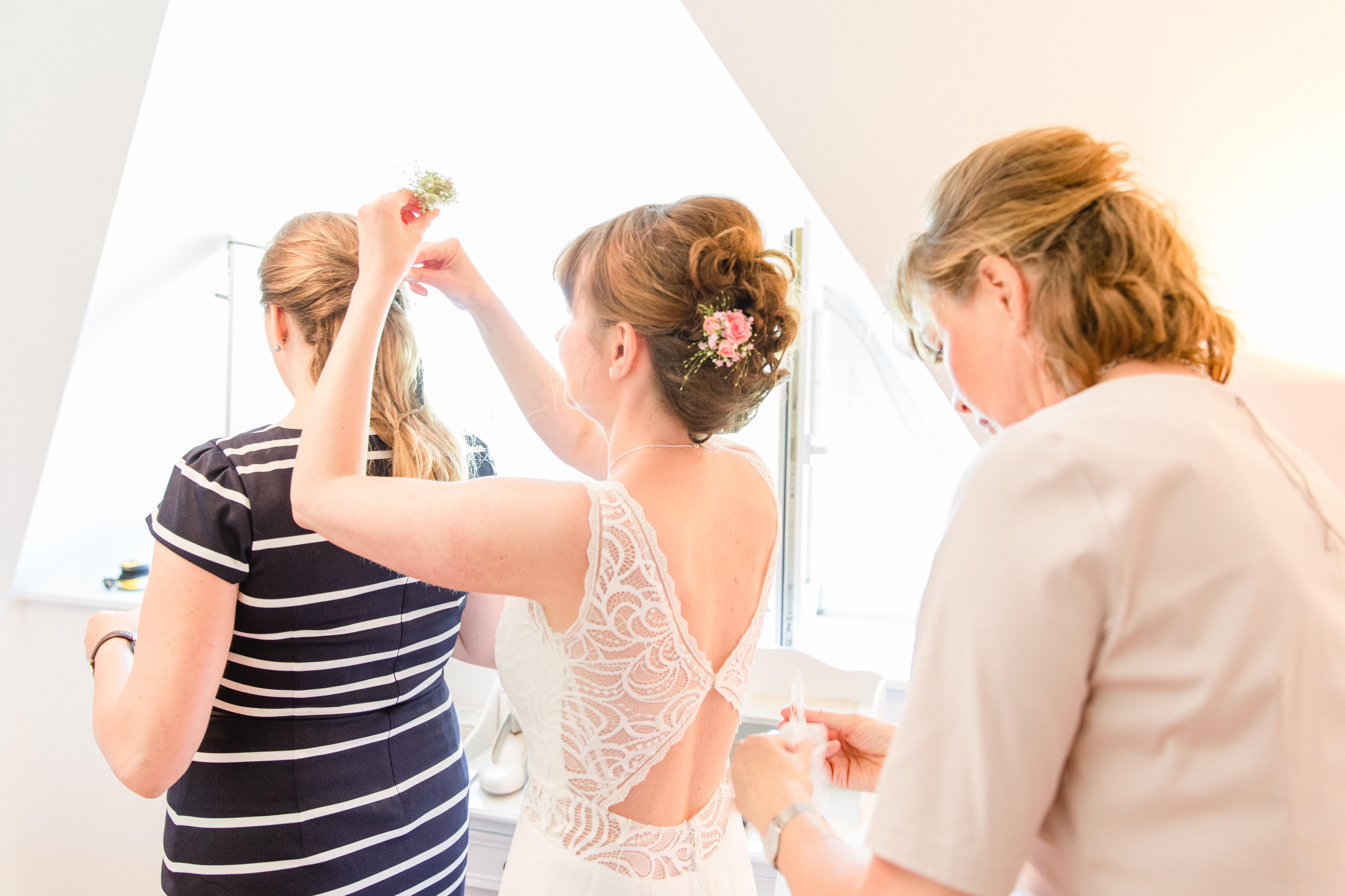 Mädels helfen sich gegenseitig beim fertigmachen für die Hochzeit.
