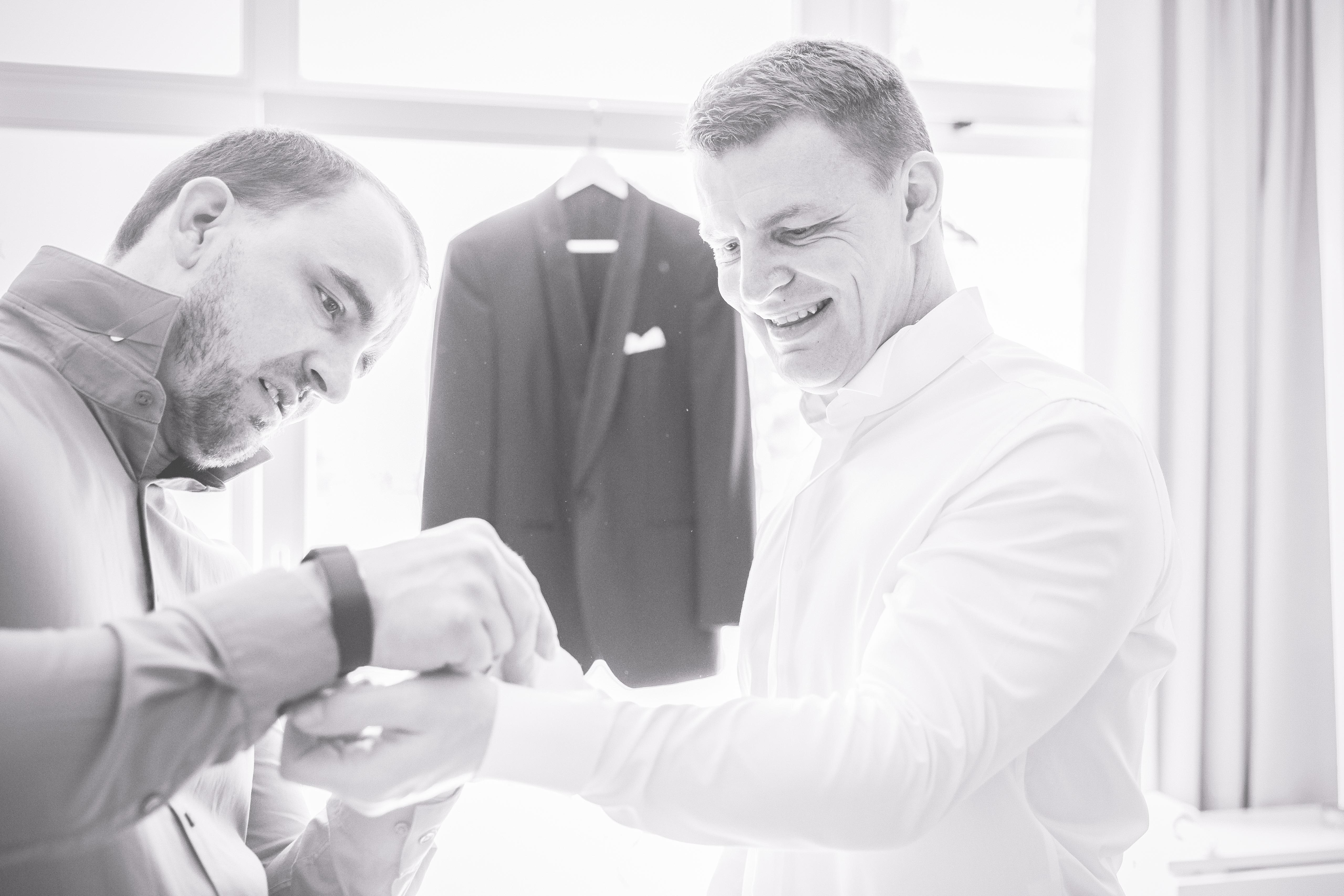 Der Bruder hilft dem Bräutigam beim Anlegen der Manschettenknöpfe.