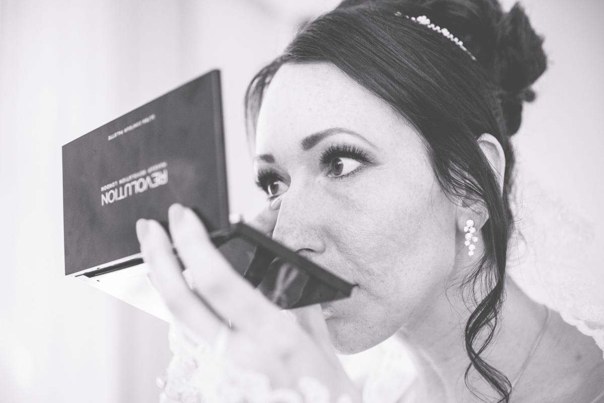 Braut überprüft das Make-up vor der Trauung.