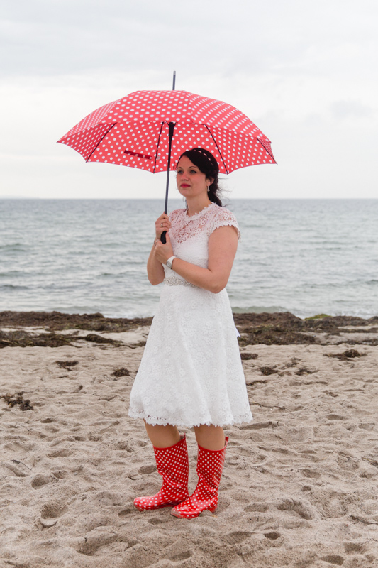 Braut mit Gummistiefeln und Regenschirm