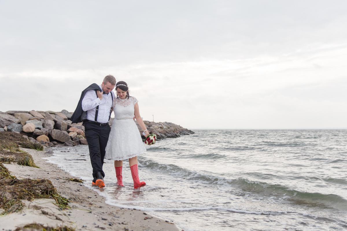 Verliebtes Paar mit Gummistiefeln am Meer