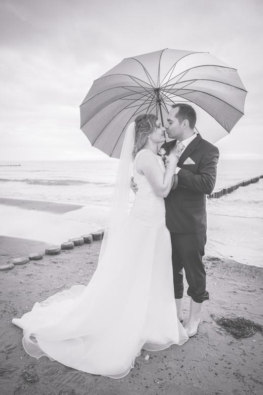 Brautpaar mit Regenschirm.