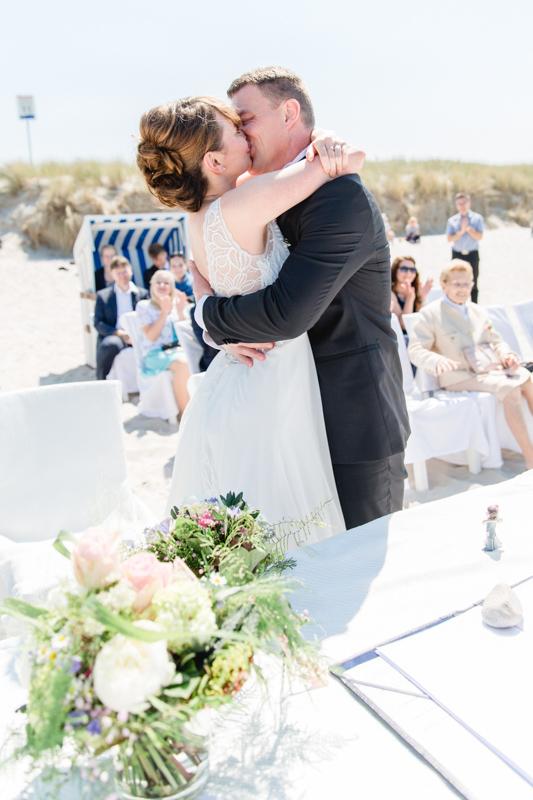 Küssendes Paar bei Strandhochzeit.