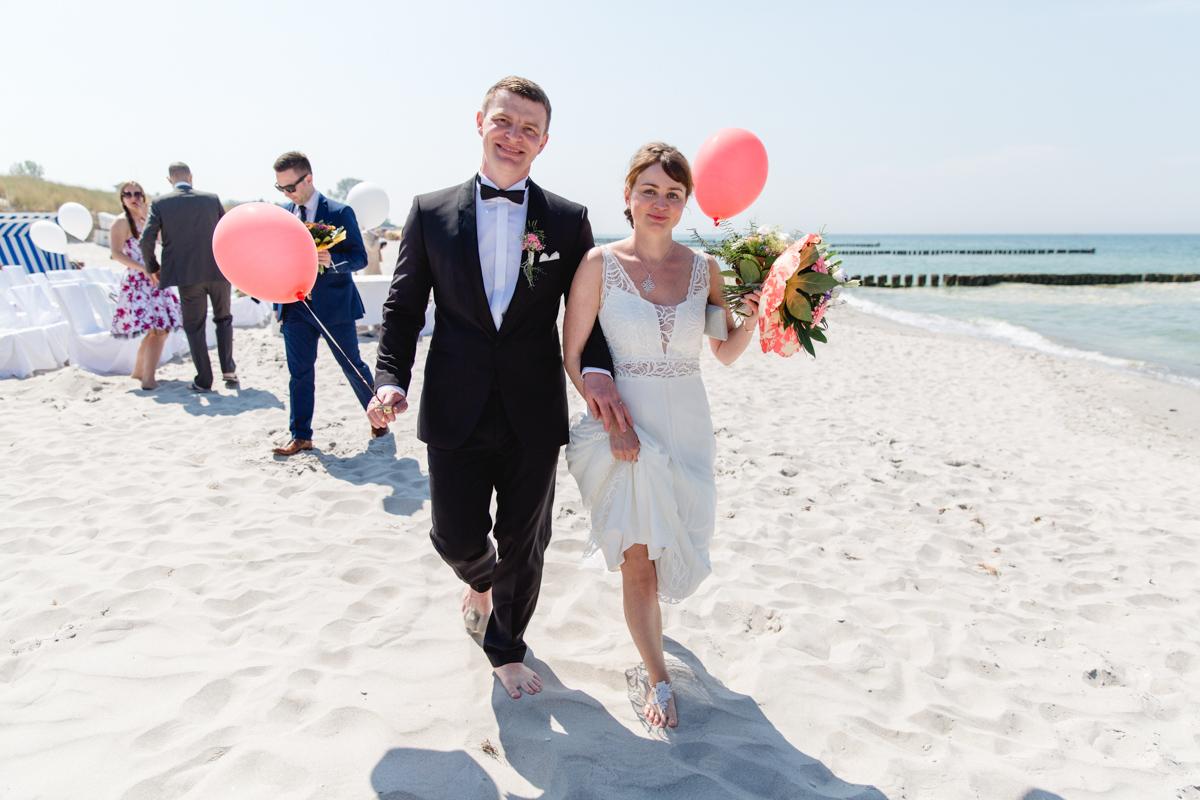 Brautpaar mit Luftballons am Strand.