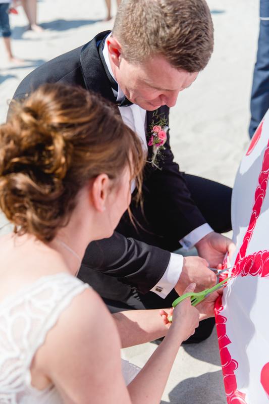 Gemeinsam schneidet das Brautpaar ein Herz aus.