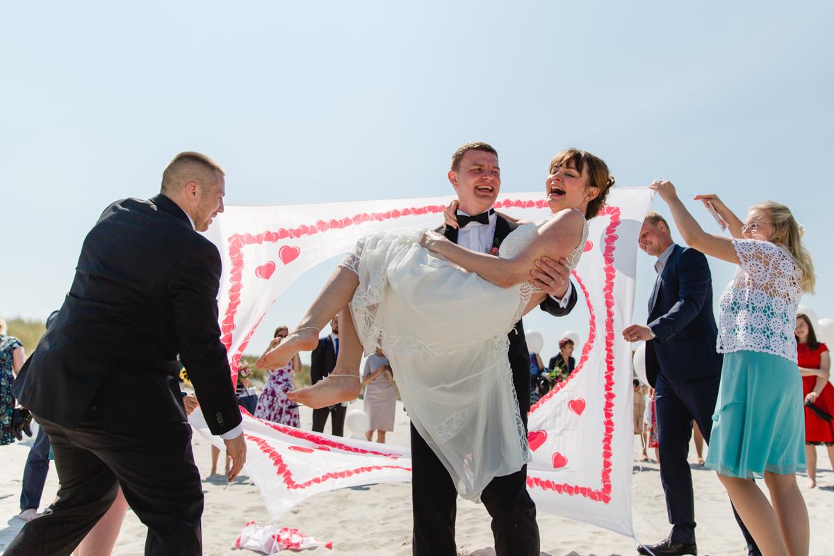 Bräutigam trägt seine Braut durch ein Stoffherz.