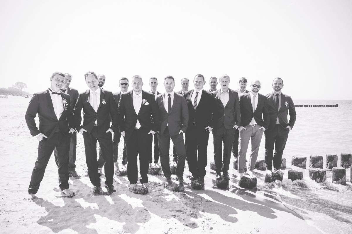 Gruppenfoto mit Männern am Strand.