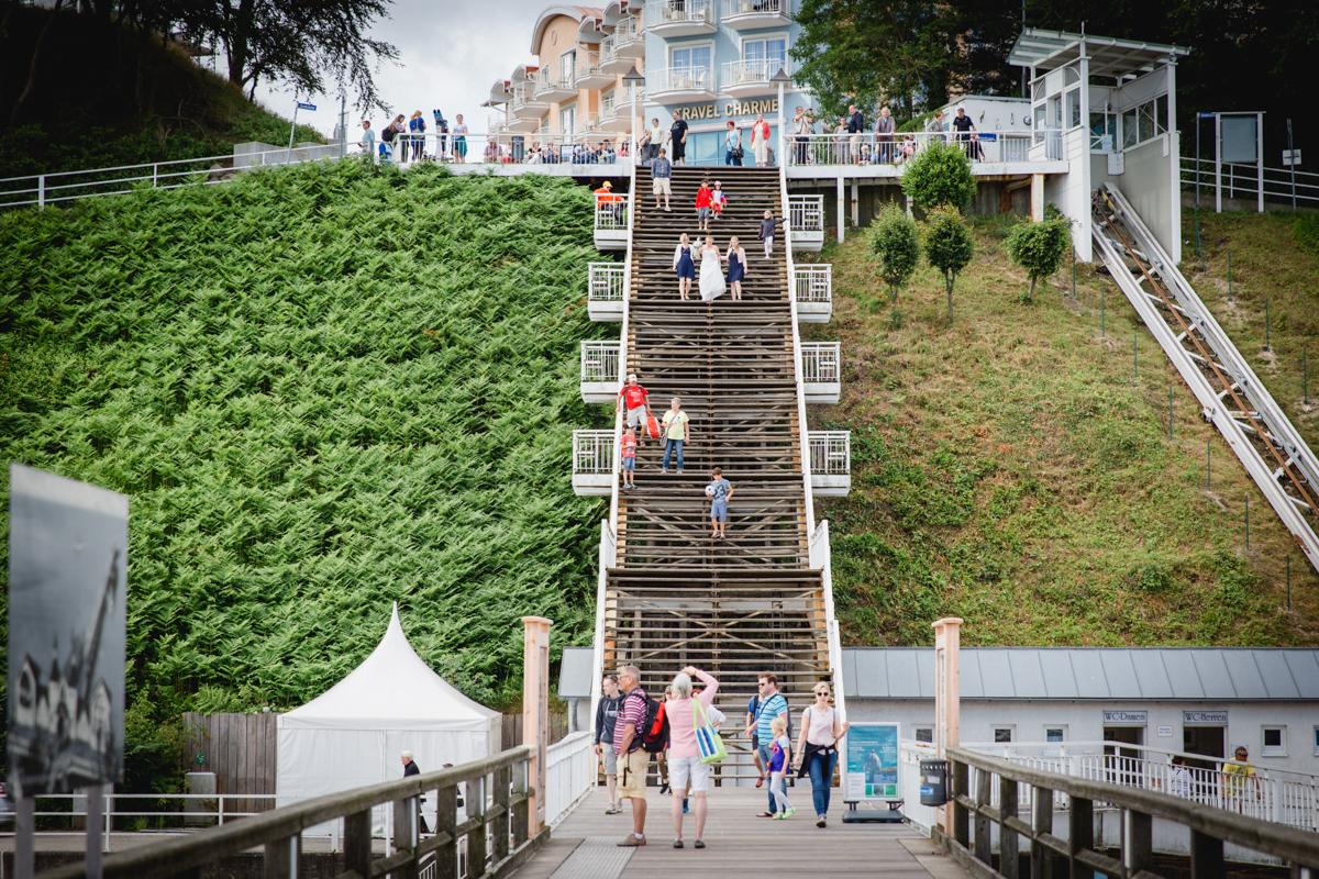 Braut kommt die Treppe vorm Standesamt Sellin runter gelaufen.