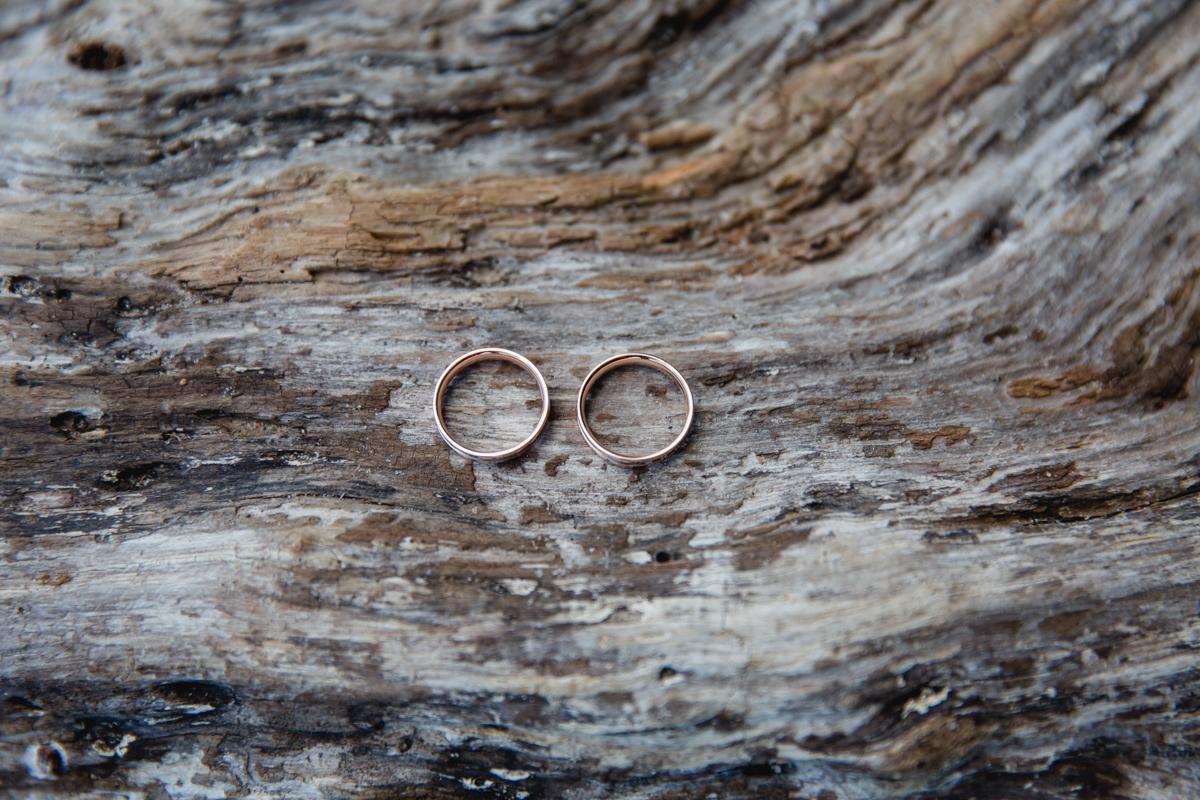 Hochzeitsfoto von den Eheringen auf einem Baumstamm.