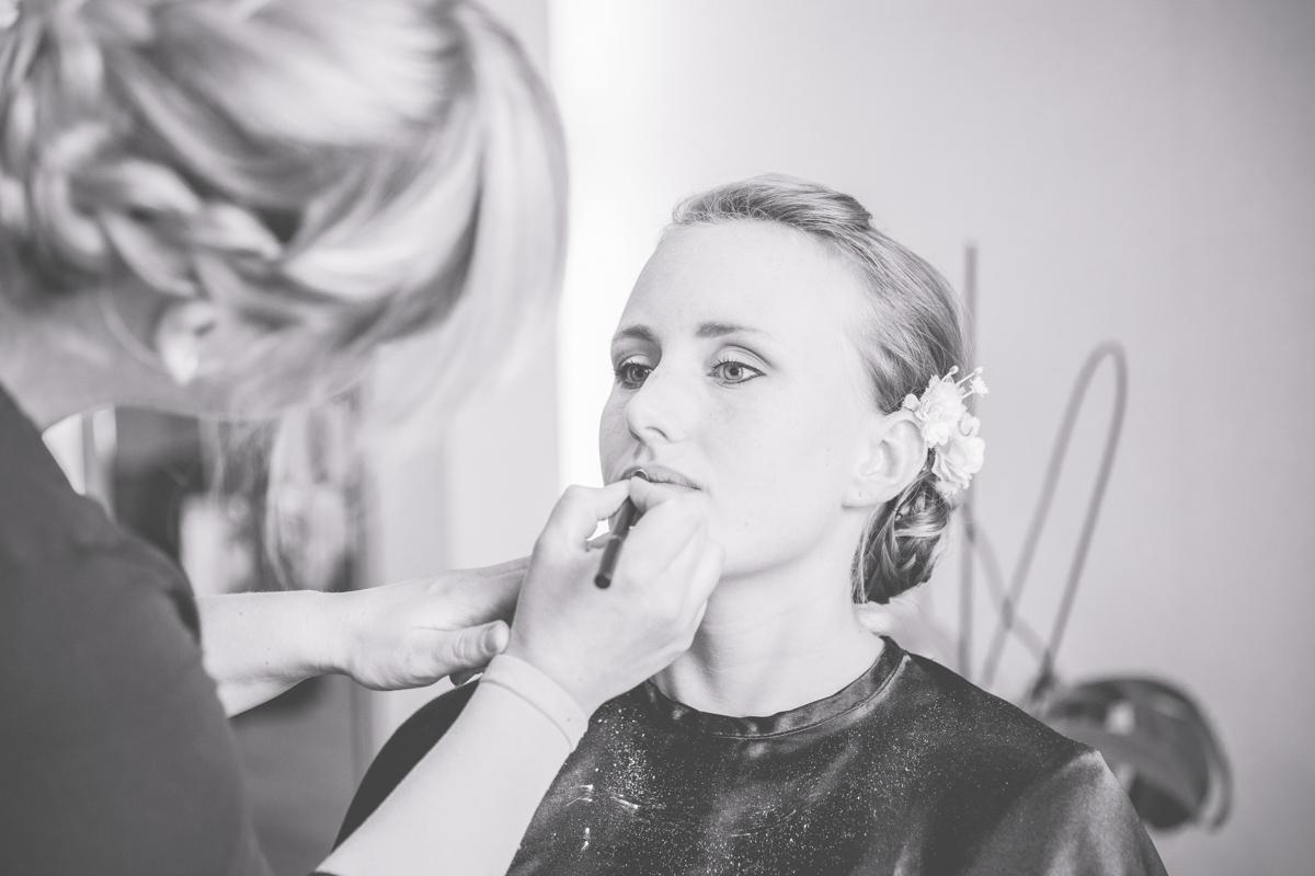 Foto wie die Braut beim Friseur geschminkt wird.