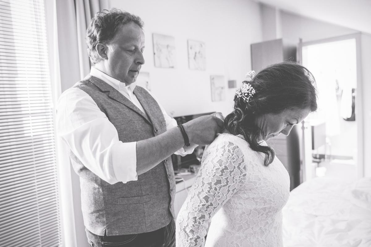 Bräutigam hilft der Braut in ihr Kleid.
