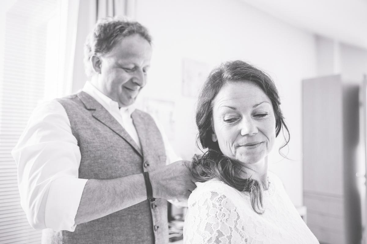Bräutigam legt die Kette der Braut an.