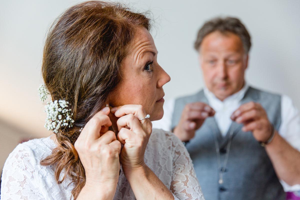 Braut legt ihre Ohrringe an.