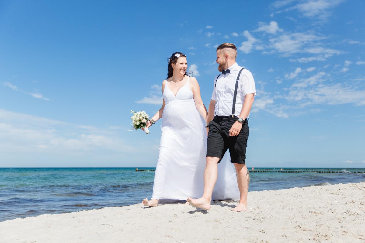 Schwangere Braut und Bräutigam am Strand.