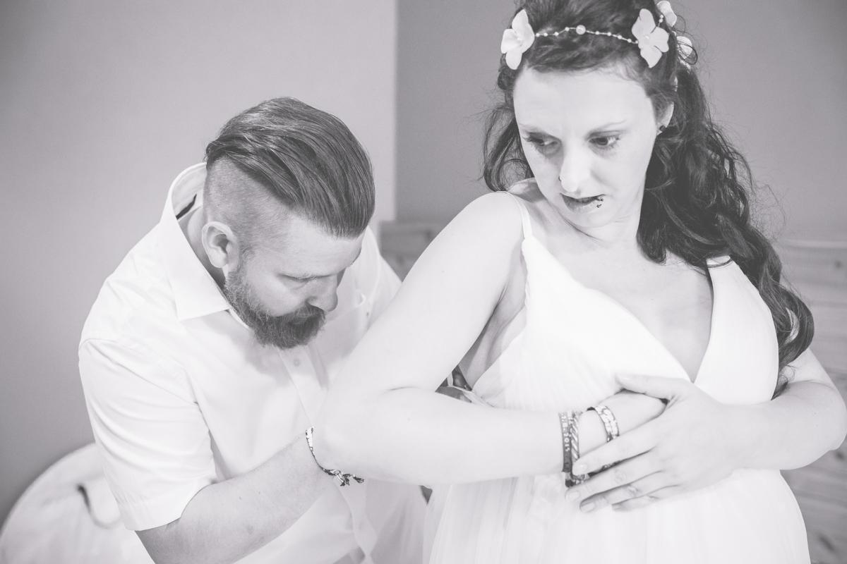 Bräutigam hilft Braut beim Fertigmachen.