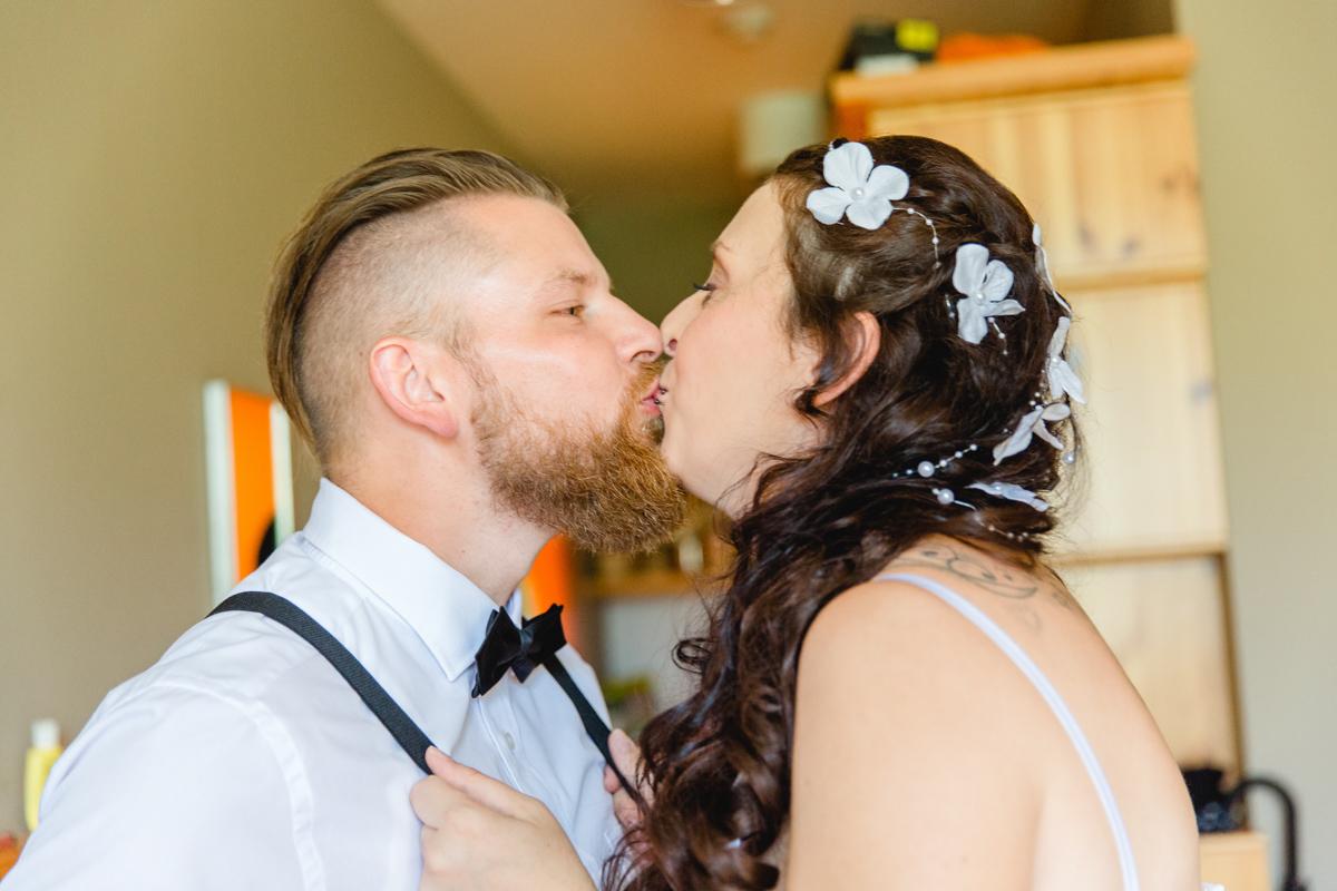 Braut und Bäutigam helfen sich beim Anziehen.