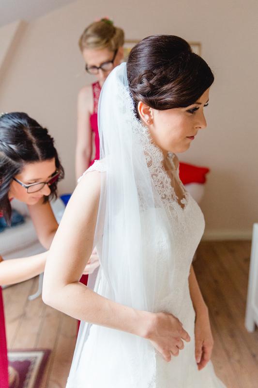 Die Trauzeugin hilft der Braut in ihr Brautkleid.