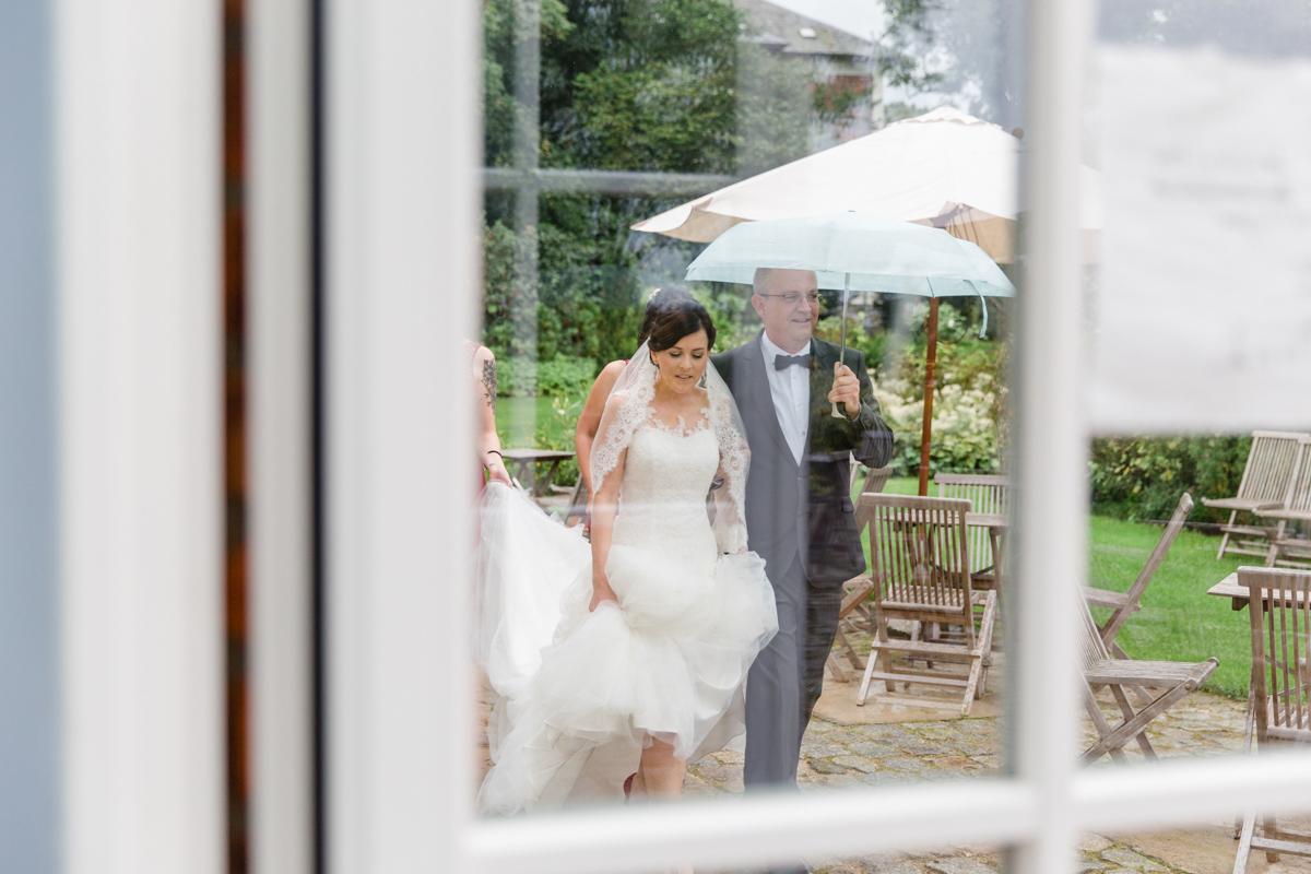 Braut eilt durch den Regen zur Trauung.