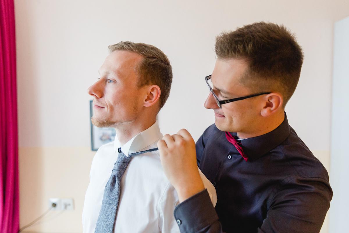 Der Trauzeuge hilft dem Bräutigam die Krawatte anzulegen.