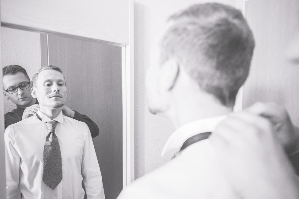 Bräutigam legt seine Krawatte an.