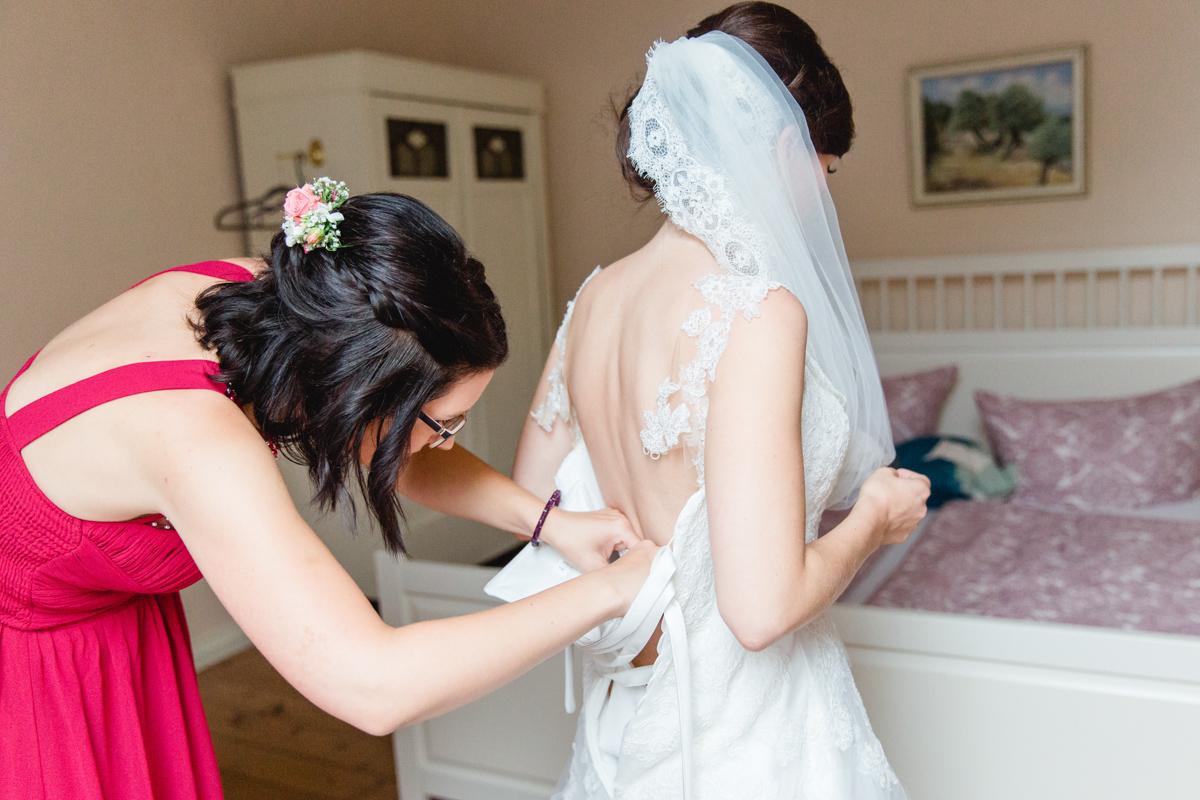 Die Trauzeugin hilft der Braut ins Brautkleid.