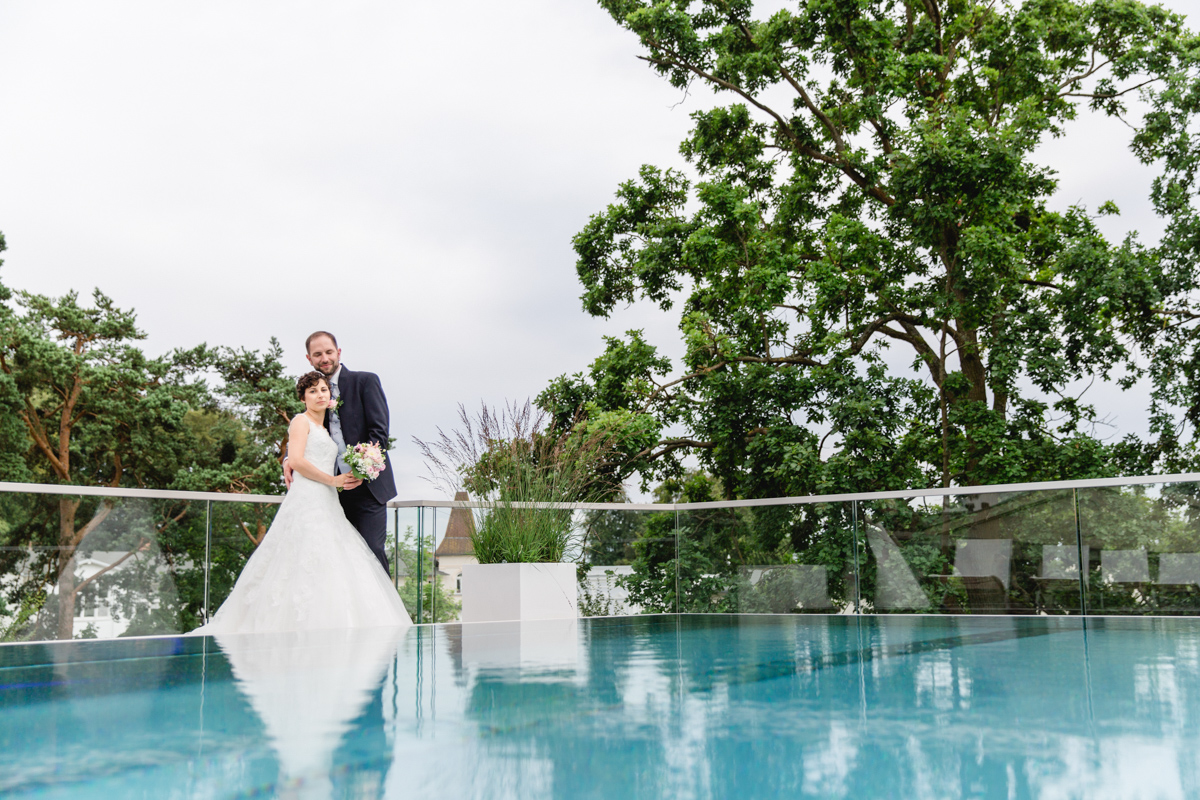 Brautpaar steht am rooftop Pool