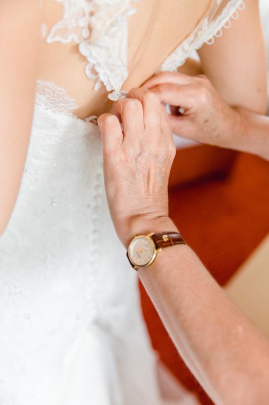 Hochzeitsfoto Brautkleid wird geschlossen.