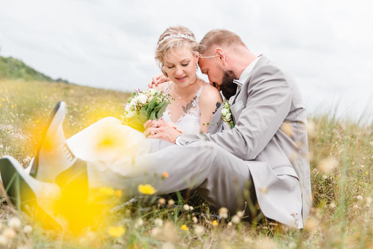 Brautpaar sitzt auf einer Düne.