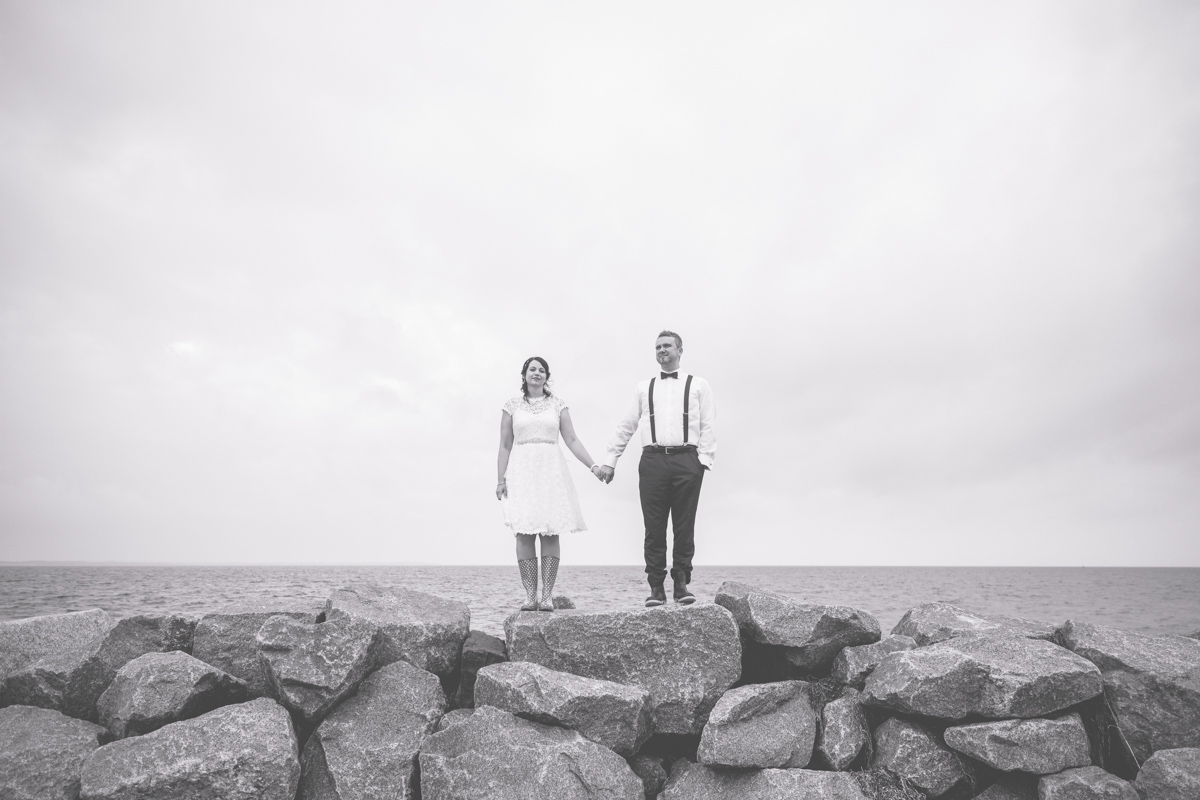 Brautpaar steht auf einer Steinmauer an der Ostsee.