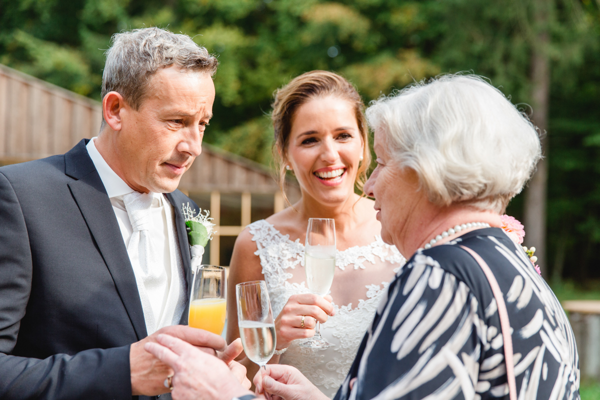 Brautpaar beim Anstoßen mit den Gästen.